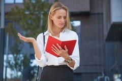 Rozczarowanej blondynki biznesowa kobieta z notatnikiem przeciw budynkowi biurowemu zdjęcia royalty free