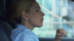 Rozczarowany bizneswoman zdejmuje szkła, siedzi w samochodzie, spęczenie z niepowodzeniem zbiory