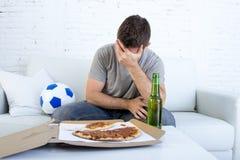 Rozczarowany mężczyzna dopatrywania mecz futbolowy na telewizyjny desperacki i smutnym Zdjęcie Royalty Free