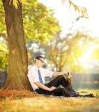 Rozczarowany mężczyzna obsiadanie na trawie z butelką w jego ręce, wewnątrz zdjęcie stock