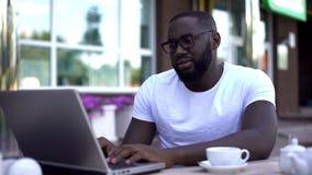 Rozczarowany mężczyzna sprawdza emaila na laptopu komputerze osobistym w plenerowej kawiarni, odbiorcza zła wiadomość fotografia royalty free