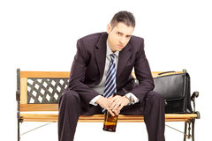 Rozczarowany młody biznesmena obsiadanie na drewnianej ławce z bo zdjęcia stock