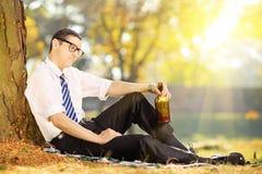 Rozczarowany młody biznesmena obsiadanie na trawie z butelką wewnątrz fotografia stock