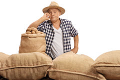 Rozczarowany starszy rolnik pozuje z burlap workami fotografia royalty free