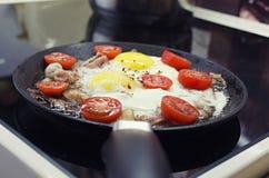 Rozdrapani jajka gotuje w sma?y niecce, gotuje na ceramicznej kuchence, sma?yli jajka z bekonem i pomidorem, frontowego widoku zb zdjęcie royalty free