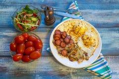 Rozdrapani jajka z bekonem, cebulą i kiełbasą, fotografia royalty free