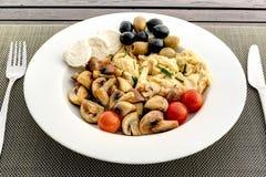 Rozdrapani jajka z pieczarkami, oliwkami i czereśniowymi pomidorami na bielu talerzu, Zdjęcie Royalty Free