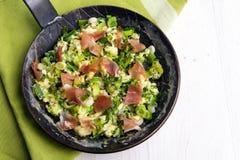 Rozdrapani jajka z zielonymi cebulami i prosciutto w czarnym żelazie Zdjęcia Royalty Free