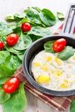 Rozdrapani przepiórek jajka z szpinakiem i pomidorami. Indoors zbliżenie. Obraz Stock