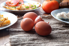 Rozdrapani, smażący, gotujący się jajka na drewnianym stole, Obraz Royalty Free