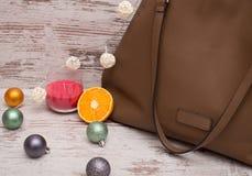 Rozdziela dużą brown damy torebkę na drewnianym tle, Bożenarodzeniowych ornamentach, girlandzie i świeczce, Obraz Royalty Free