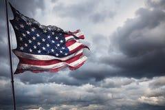 Rozdzierający łzy grunge stary zbliżenie amerykańska usa flaga, gwiazdy i lampasy, zlani stany America na chmurnym niebie, ciemna Obraz Royalty Free