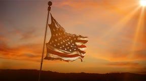 Rozdzierający łzy grunge usa starzy amerykańscy flaga, gwiazdy i lampasy przy zmierzchem, z słońce promieniami zaświecamy Zdjęcia Royalty Free