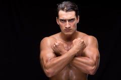Rozdzierający mięśniowy przystojny mężczyzna na czarnym tle Obrazy Stock