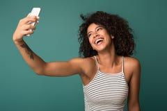Roześmiana afroamerykańska kobieta bierze selfie na tle zdjęcia royalty free