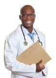 Roześmiana afrykanin lekarka z książeczką zdrowia w jego ręce Fotografia Stock