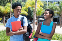 Roześmiana amerykanin afrykańskiego pochodzenia samiec i żeński uczeń na kampusie u Zdjęcie Royalty Free