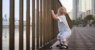 Roześmiana chłopiec stoi w a w wieku 1 roku dancingowego mienia uczenie i robić pierwszym krokom poręcz chodzić zbiory