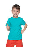 Roześmiana chłopiec trzyma jego kciuk up Fotografia Stock