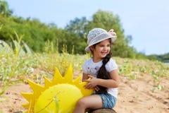 Roześmiana ciemnowłosa dziewczyna pozuje w parku Zdjęcie Royalty Free