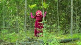 Roześmiana czarownica w lesie wykonuje obrządkowego tana z gałąź paproć zdjęcie wideo