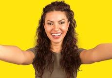 Roześmiana dziewczyna bierze selfie na kolorze żółtym obraz royalty free
