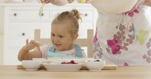 Roześmiana dziewczyna z słodka bułeczka rodzicem w fartuchu i filiżankami zbiory