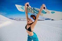 Roześmiana emocjonalna młoda kobieta trzyma snowboard w jej rękach w zimie w kapeluszu i swimsuit sport ekstremalny euphrates Kob zdjęcie stock