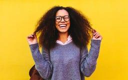Roześmiana kędzierzawa z włosami kobieta na żółtym tle obrazy stock