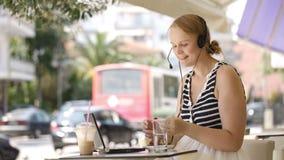 Roześmiana kobieta jest ubranym słuchawki w plenerowej kawiarni zbiory