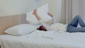 Roześmiana kobieta spada w łóżko i bawić się z poduszkami zbiory wideo