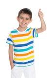 Roześmiana młoda chłopiec trzyma jego kciuk up Obrazy Stock