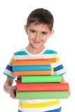 Roześmiana młoda chłopiec z książkami zdjęcie royalty free