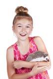 Roześmiana młoda dziewczyna ma zabawę z jej zwierzę domowe jeżem obraz stock