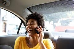 Roześmiana młoda kobieta opowiada na telefonie komórkowym w samochodzie Zdjęcia Royalty Free