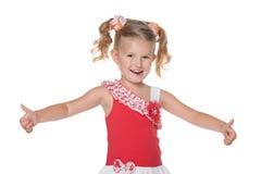 Roześmiana mała dziewczynka trzyma jej aprobaty Zdjęcia Royalty Free