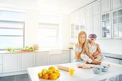 Roześmiana matka wpólnie i córka w kuchni zdjęcia royalty free