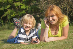 Roześmiana matka z jej synem kłama w ogródzie. Zdjęcie Stock