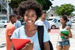 Roześmianego amerykanina afrykańskiego pochodzenia żeński uczeń z grupą przyjaciele obrazy stock