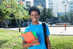 Roześmianego amerykanina afrykańskiego pochodzenia męski uczeń patrzeje kamerę Fotografia Royalty Free