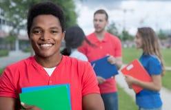Roześmianego amerykanina afrykańskiego pochodzenia męski uczeń z ścierniskowymi i wieloetnicznymi przyjaciółmi Zdjęcie Royalty Free