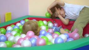 Roześmianej ślicznej blondynki preschool caucasian berbeć bawić się w wielo- coloured balowym basenie dzieciniec zbiory