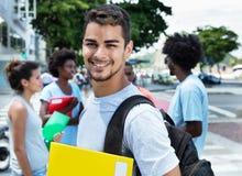 Roześmiany łaciński męski uczeń z grupą przyjaciele zdjęcie stock