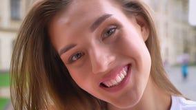 Roześmiany ładny caucasian żeński patrzeć prosto przy kamerą z szczerym uśmiechem plenerowym, słoneczny dzień