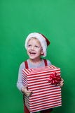 Roześmiany śmieszny dziecko w Santa czerwonego kapeluszowego mienia Bożenarodzeniowym prezencie w ręce Bożenarodzeniowy pojęcie Fotografia Stock