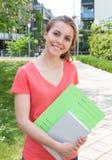 Roześmiany żeński uczeń w czerwonej koszula na kampusie zdjęcia royalty free