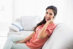 Roześmiany brunetki obsiadanie na jej kanapie na telefonie patrzeje ca Fotografia Royalty Free