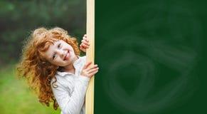 Roześmiany dziecko z szkolnym blackboard pokazuje zdrowego białego Teet Zdjęcia Stock