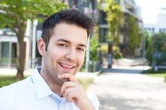 Roześmiany latynoski męski uczeń patrzeje kampus Zdjęcia Stock