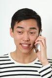 Roześmiany młody Azjatycki mężczyzna używa smartphone obraz stock